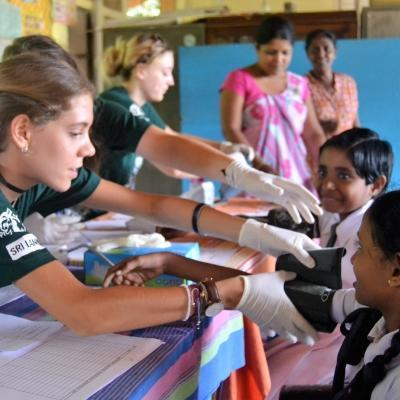A young girl has her blood pressure taken on Projects Abroad's medical internship for high school students in Sri Lanka